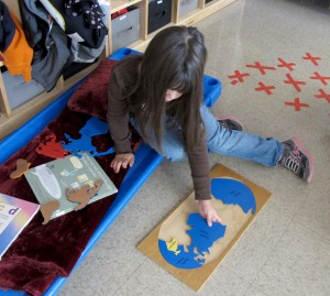 A student works on a map puzzle at Busy Bees Academy, a public preschool in Columbus, Ind.