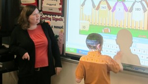 A teacher at East Side Intermediate School in Anderson directs a student as he uses a smart board in math class.