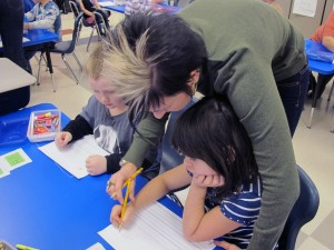 Lisa Coughanowr, a kindergarten teacher at East Side Elementary in Brazil, helps a student draw a classmate.