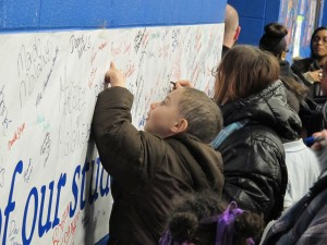 A young boy signs his name to a poster advocating for Gary's Charter School of the Dunes to remain open. Ball State University officials have revoked the school's charter.