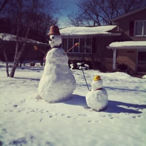 A snowman with his snowson on a leash.