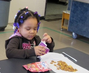 A Head Start student opens her milk in the cafeteria of Evans Elementary in Lake Station. Students eat a healthy snack before they go home for the day.