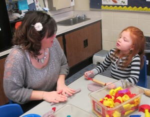 A Head Start classroom aide asks a student to make shapes in her play dough.