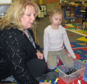 Head Start teacher Kathy Ammerman helps a student put together a puzzle.