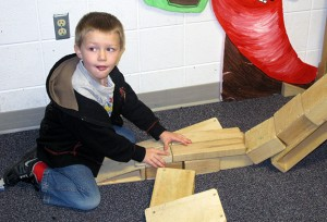 A child builds a bridge with blocks at the Monroe County United Ministries childcare center.