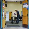 A voter stands in a voting booth.
