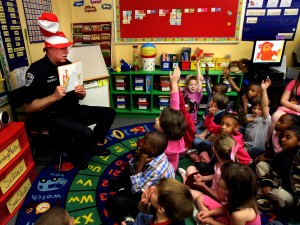 A school resource officers reads a Dr. Seuss book to first graders. Safety experts say having trained police officers deeply involved in the education community can help neutralize violence in schools.