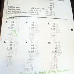 A math worksheet emphasizes the 'partial sums' method of solving addition problems.