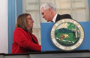Rep. Rhonda Rhoads shakes Gov. Mike Pence's hand as he takes the podium for a speech in Corydon.