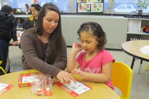 An aide helps a student count at Busy Bees Academy, a public preschool in Columbus.