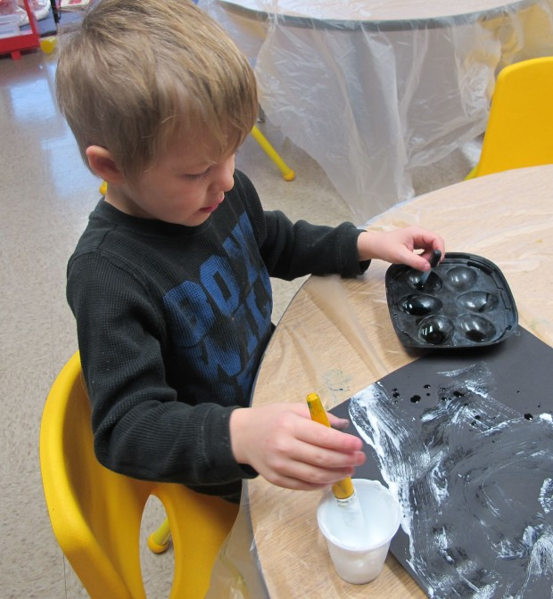 A student uses a large brush and a small eyedropper to create puff paint art at Busy Bees Academy, a public preschool in Columbus.