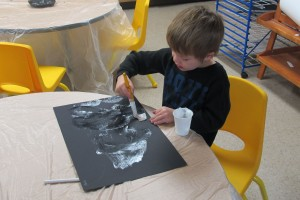 A student paints an art project at Busy Bees Academy, a public preschool in Columbus.