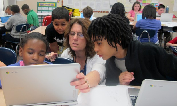 Warren Township fourth grade teacher Fatonia Shank and her students crow around a laptop to look at a document. Students were working on stories after a peer-writing exercise.