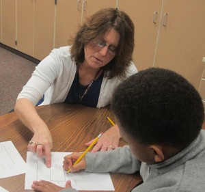 Fourth grade teacher Fatonia Shank helps a student with a perimeter problem.