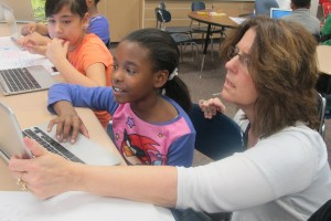 Fatonia Shank, a fourth grade teacher in Warren Township, helps a student with a writing exercise.