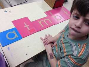 A four year old in Eve Cusack's class at Bloomington Montessori School practices his letter sounds by tracing over the sandpaper letter blocks.
