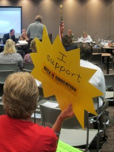 A crowd member shows her support for State Superintendent Glenda Ritz during July's State Board of Education meeting. (Photo Credit: Rachel Morello/StateImpact Indiana)