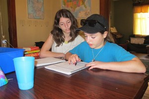 Emily (left) and Holli Burnfield work on language arts lessons together. The girls are homeschooled, along with their younger sister Layla, in Bloomfield.