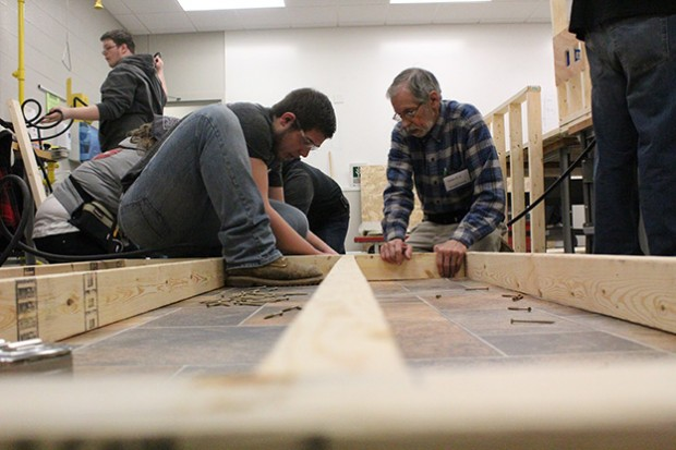 Ivy Tech students Riley Sullivan, left, and Arnold Dorey assemble part of an exterior wall during a class building simulation. (Photo Credit: Rachel Morello/StateImpact Indiana)