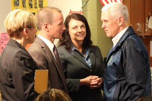 Gov. Mike Pence (right) greets Early Learning Indiana CEO Ted Maple (second from left) and Melanie Brizzi of the FSSA (second from right) at Wayne Township Preschool Thursday. (Photo Credit: Rachel Morello/StateImpact Indiana)