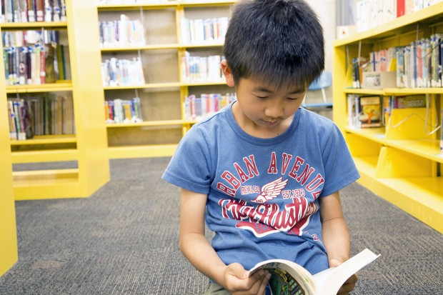 Nine-year-old Yoki Murabayashi reads a book in Japanese, his native language.