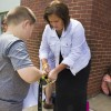Argos superintendent Michele Riise helps a student tie his shoes on the last day of the 2015-16 school year. During the first half of the year, Argos schools lost 26 students. (Peter Balonon-Rosen/Indiana Public Broadcasting)