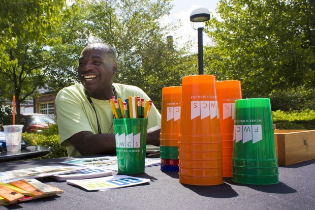 Carl Kelsaw hands out registration information and cups, rulers and pencils emblazoned with district logos outside the Allen County Public Library. (Peter Balonon-Rosen/Indiana Public Broadcasting)