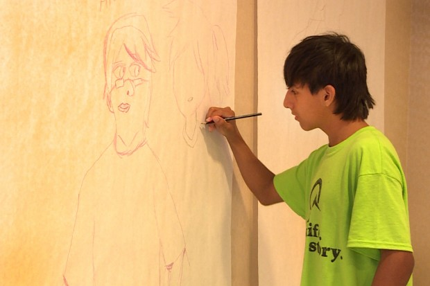 A camper at Latino Youth Summit works on a self portrait. (Claire McInerny/Indiana Public Broadcasting)