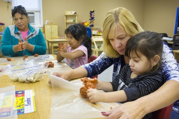 Students at the migrant preschool center create clay versions of themselves. Migrant education coordinator Debbie Gries assists a student. (Peter Balonon-Rosen/Indiana Public Broadcasting)