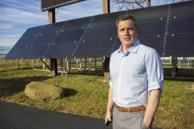 Bob McKinney stands in front of a solar panel at Johnson Melloh headquarters in Indianapolis. (Peter Balonon-Rosen/Indiana Public Broadcasting)