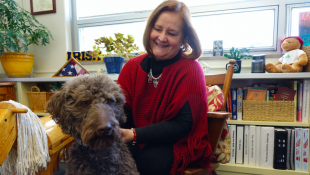 Rebecca Heger, Cathedral High School's mental health and addictions counselor, looks at 2-year-old Finn, a therapy dog at the school since 2015. (photo credit: Eric Weddle/WFYI Public Media)