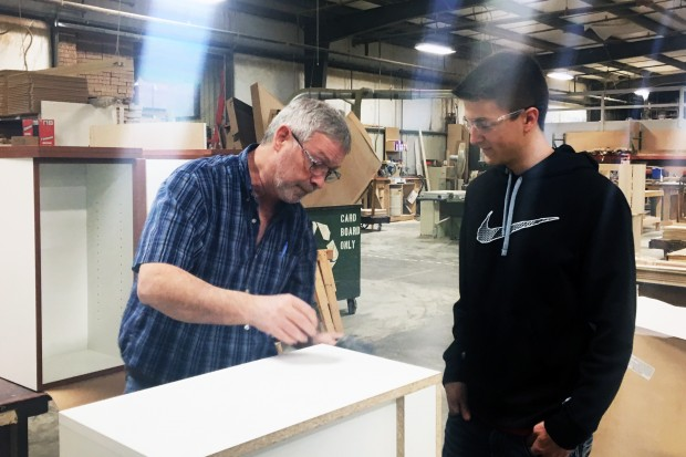 Caleb Pierson looks over a cabinet project he designed for Heartwood Manufacturing. Pierson is a graduate of a program run through Batesville High School, that helps high school students get manufacturing skills while still in high school. (photo credit: Claire...</p>						<div class=