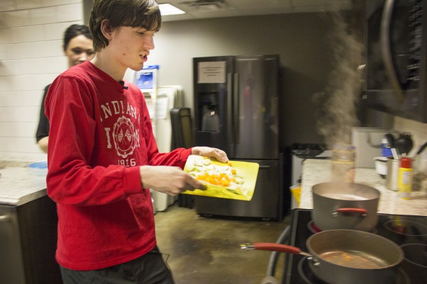 Reagan Roush carries vegetables during a cooking skills class at the College Internship Program in Bloomington. Roush is one of a growing number of college students diagnosed with autism. (Peter Balonon-Rosen/Indiana Public Broadcasting)