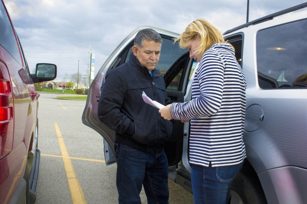 Alex Rodriguez, left, holds an informal meeting in a Wal-Mart parking lot with Debbie Gries, education coordinator for the Indiana Migrant Regional Center. (Peter Balonon-Rosen/Indiana Public Broadcasting)