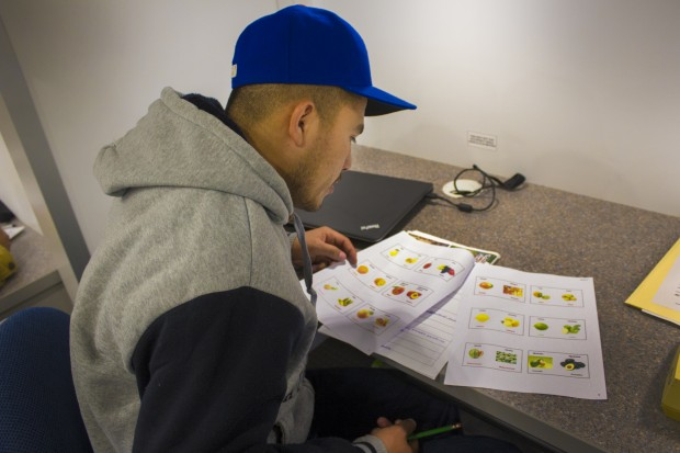 A student studies a sheet with fruits and vegetables in the Indiana Region 4 migrant education center's mobile classroom. (Peter Balonon-Rosen/Indiana Public Broadcasting)