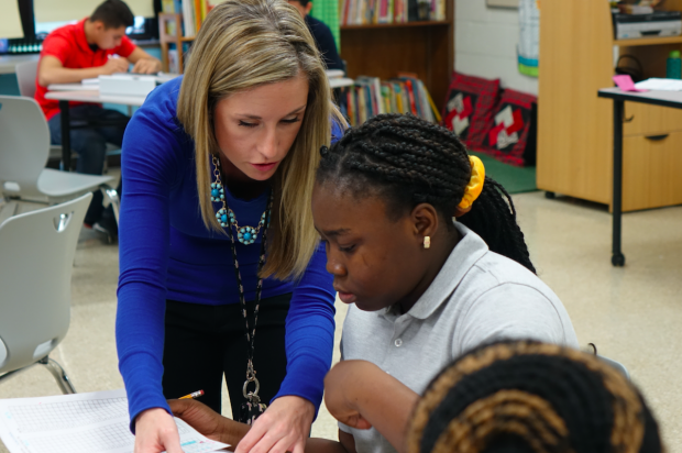 English teacher Kelly Minks works with students on pronunciation of English words during a January class at the Newcomer Program. (Eric Weddle/WFYI News)