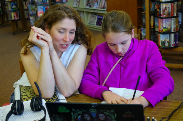 "Anna Allman laughs with daughter Piper as they review German language words as part of Piper's Hoosier Virtual Academy foreign language course at the Mooresville Public Library on April 18, 2017. Allman says she'd be devastated if the school was closed because ""individual students that are being positively impacted -- such as our family."" (Eric Weddle/WFYI News)"