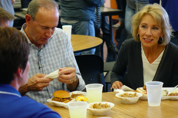 "U.S. Education Secretary Betsy DeVos and husband Dick eat at the Eastern Hancock High School cafeteria for the annual FFA hog roast fundraiser on Friday, Sept. 15, 2017 during the last stop on the ""Rethink School"" tour. (Eric Weddle/WFYI News)"