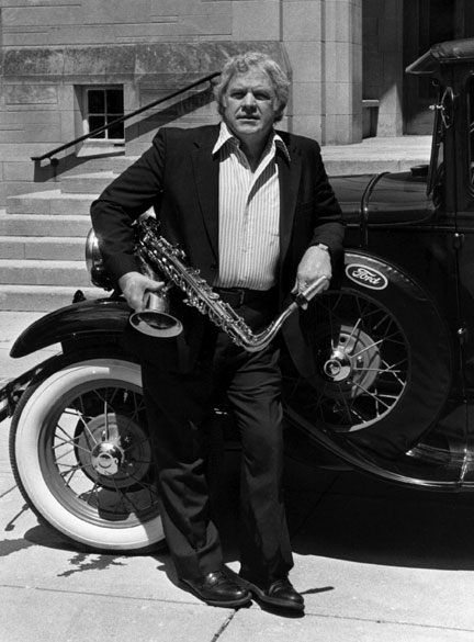 Al Cobine standing with saxophone in front of vintage car