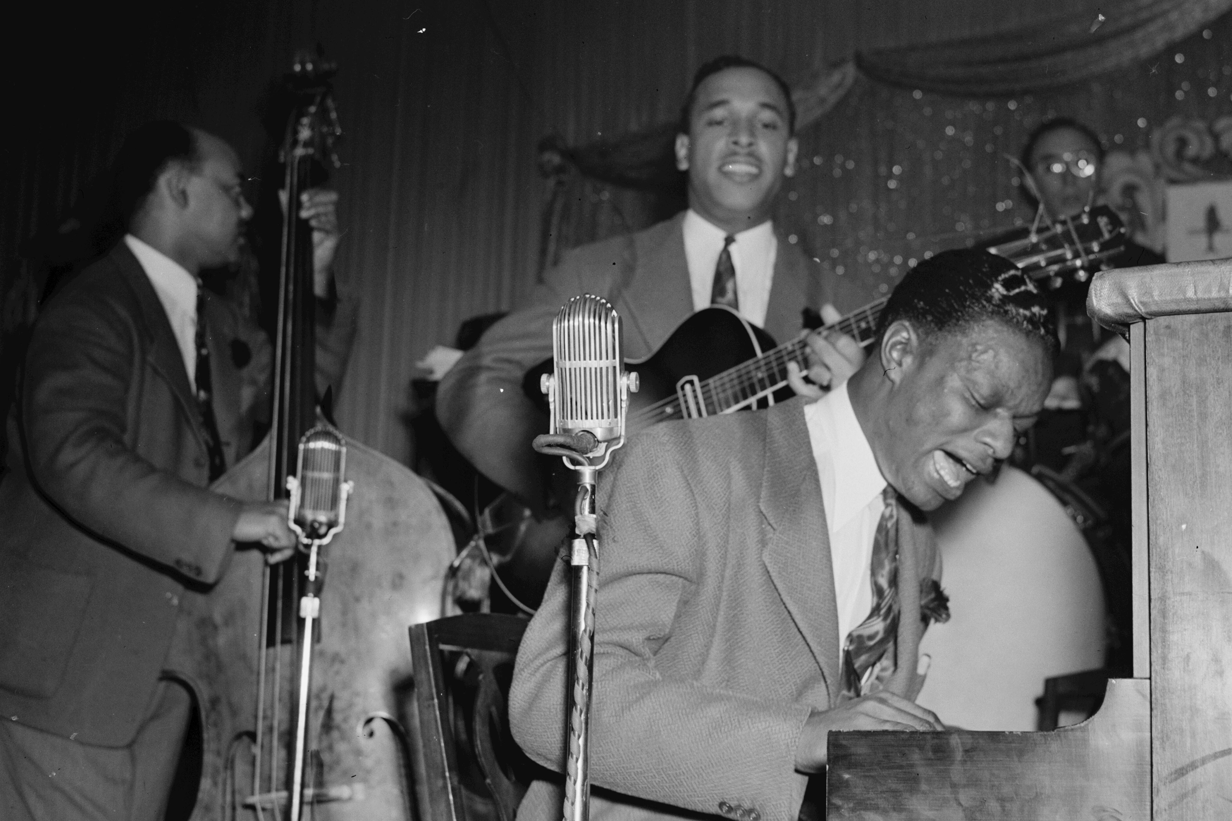 Portrait of The King Cole Trio (l–r., Wesley Prince on bass, Oscar Moore on guitar, and Nat King Cole on piano) performing at Zanzibar in New York, N.Y., ca. July 1946.