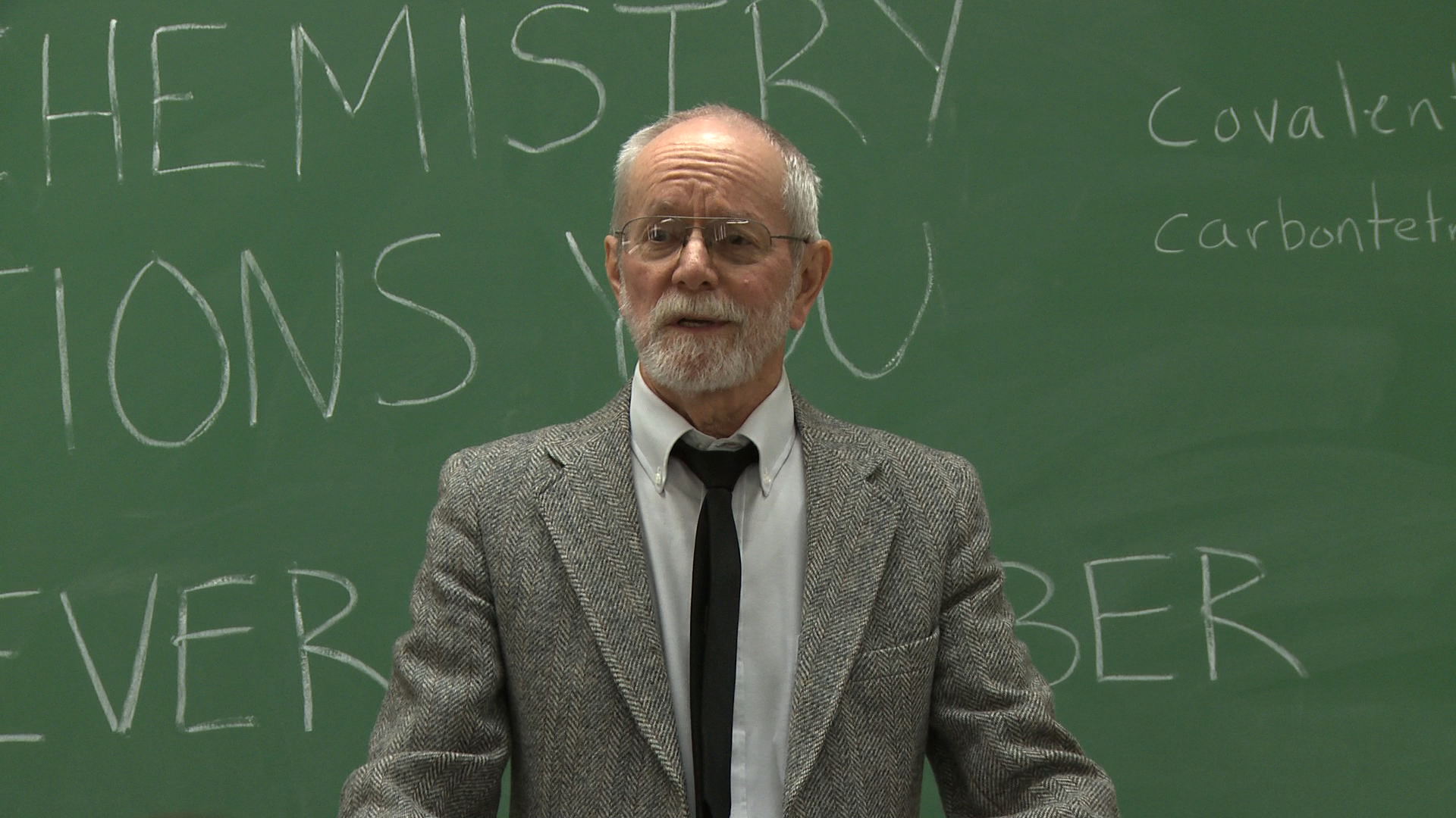 A professor standing in front of a chalkboard