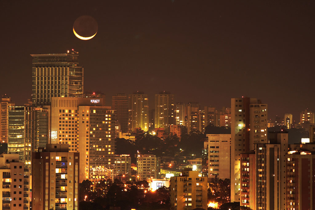 The moon shines over a brightly lit city