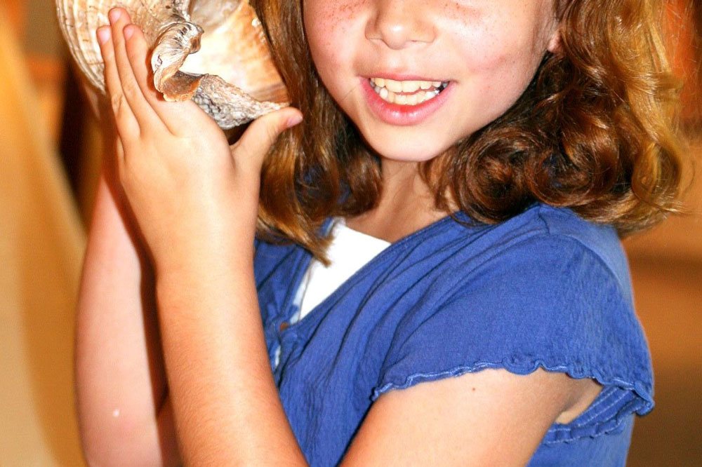 a smiling girl holds a seashell up to her ear