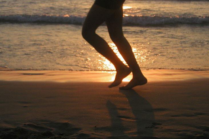 legs running on the beach at sunset