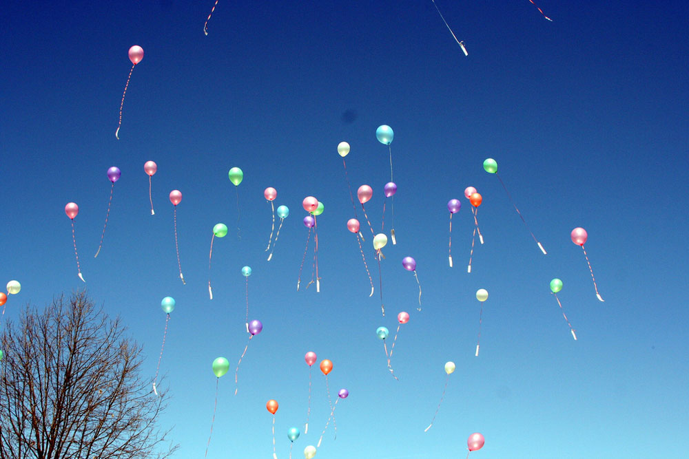 a large group of balloons floating into the air