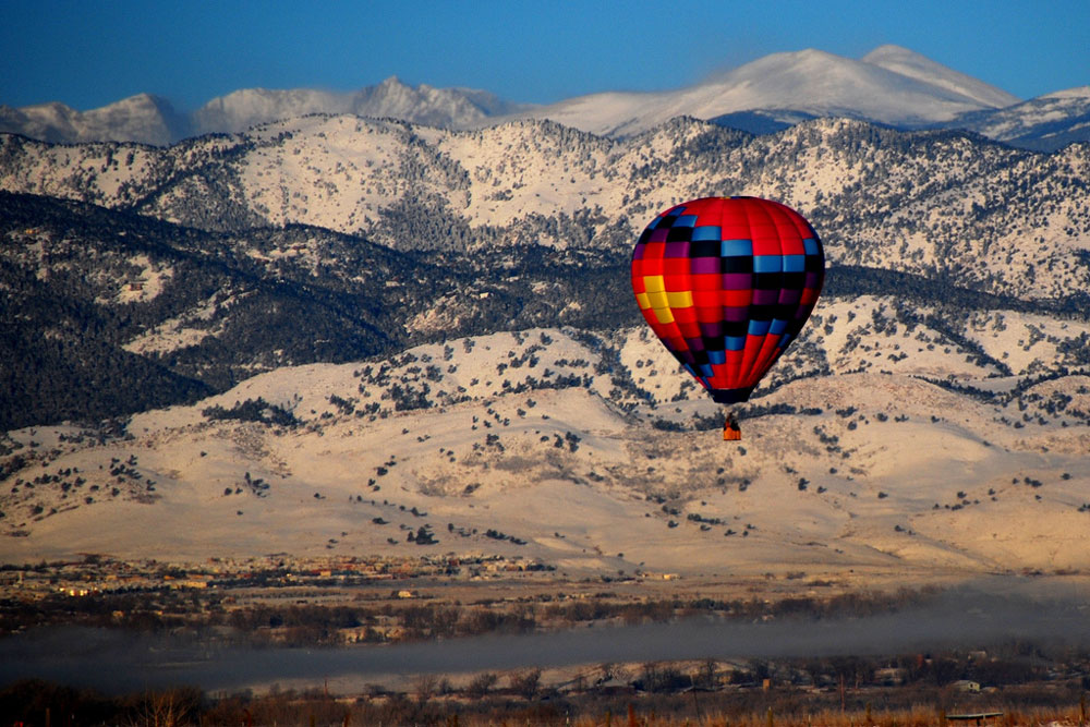 a hot air balloons flys past a snowy mountain