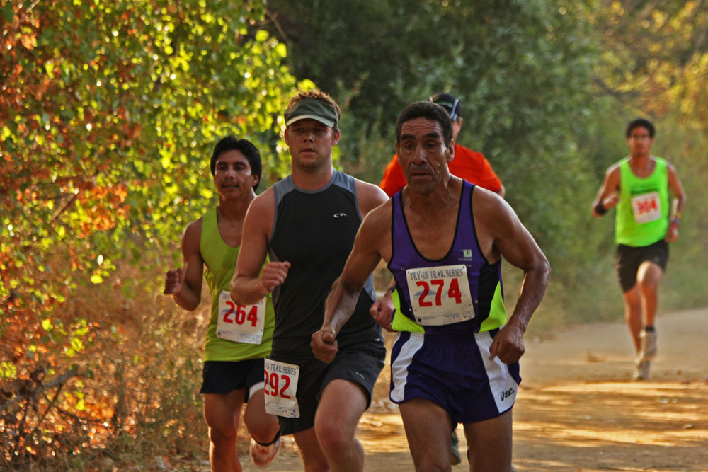 younger and older runners on a trail