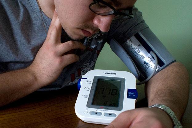 a man checks his pulse while using a blood pressure monitor