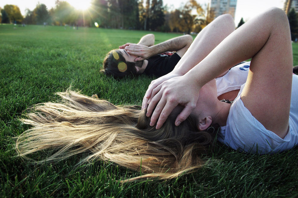 two people laying in the grass with their hands over their eyes