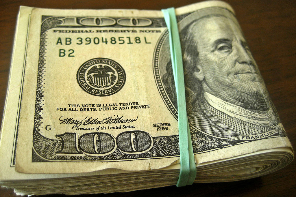 100 dollar bills tied together with a green rubberband